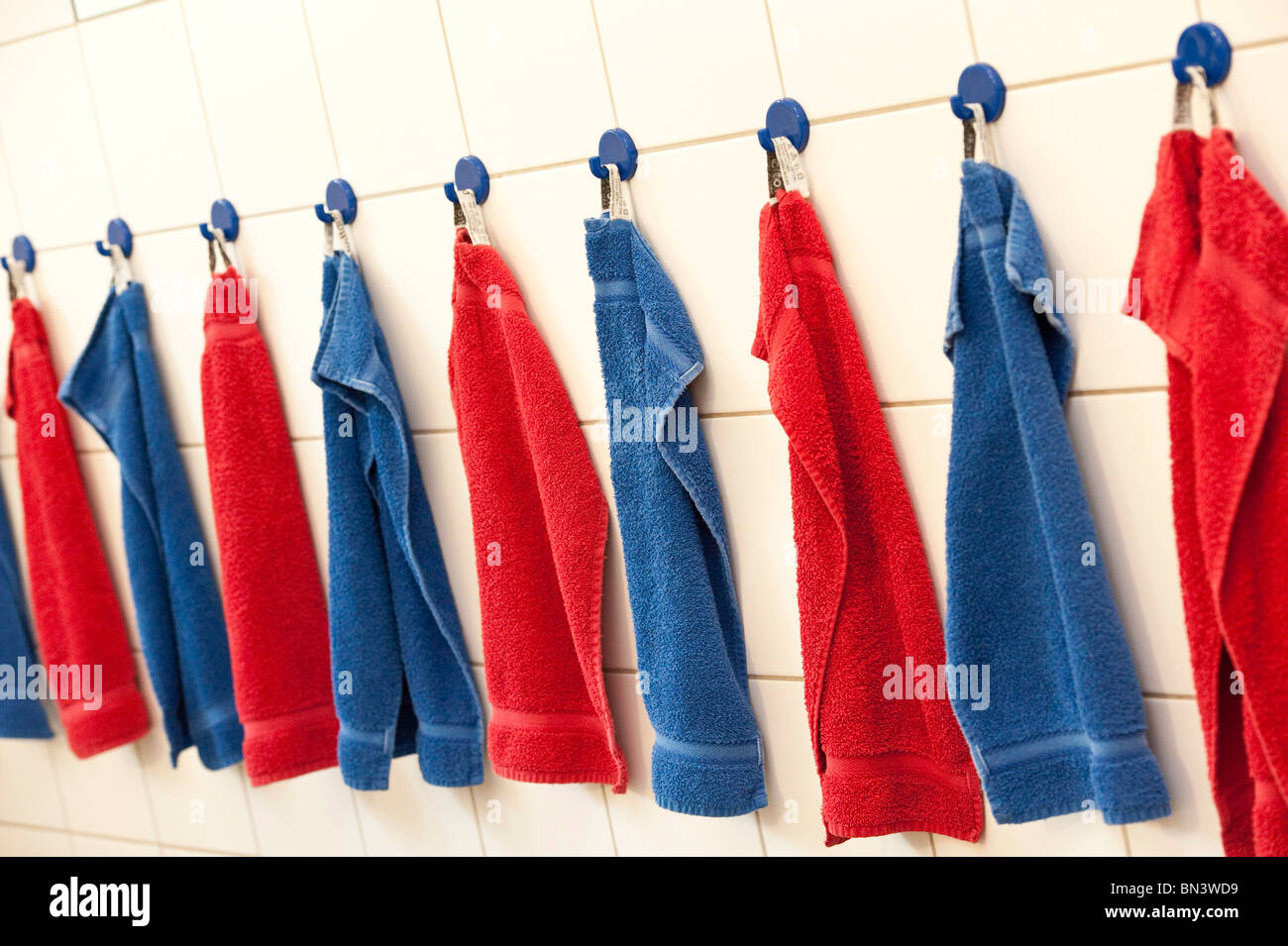 Towels hanging in a row on the wall - Stock Image