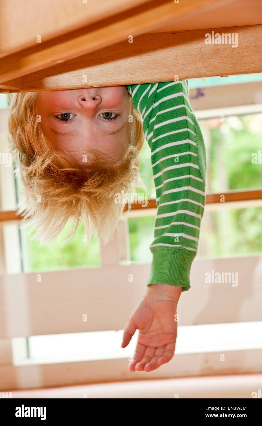 Young boy hanging upside down, low angle view - Stock Image
