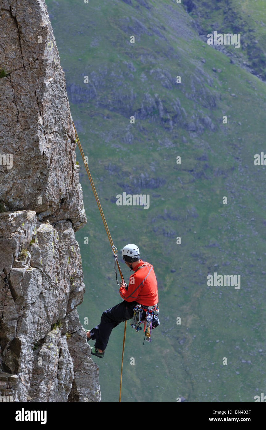 A climber abseils off the top of Napes Needle on Great Gablein the Lake District - Stock Image