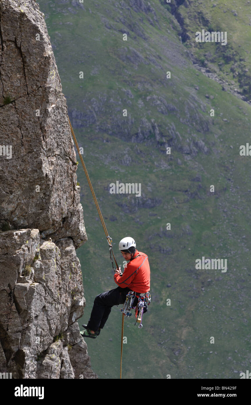 A climber abseils ( rappels) off Napes Needle on Great Gable in the Lake District - Stock Image