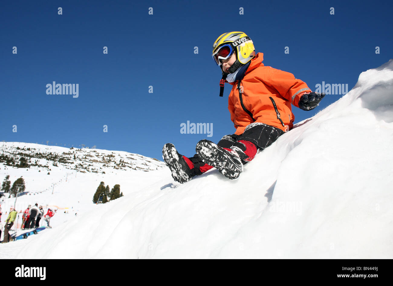 Child in safety helmet slipping down a snowy slope, Jerzens, Austria - Stock Image