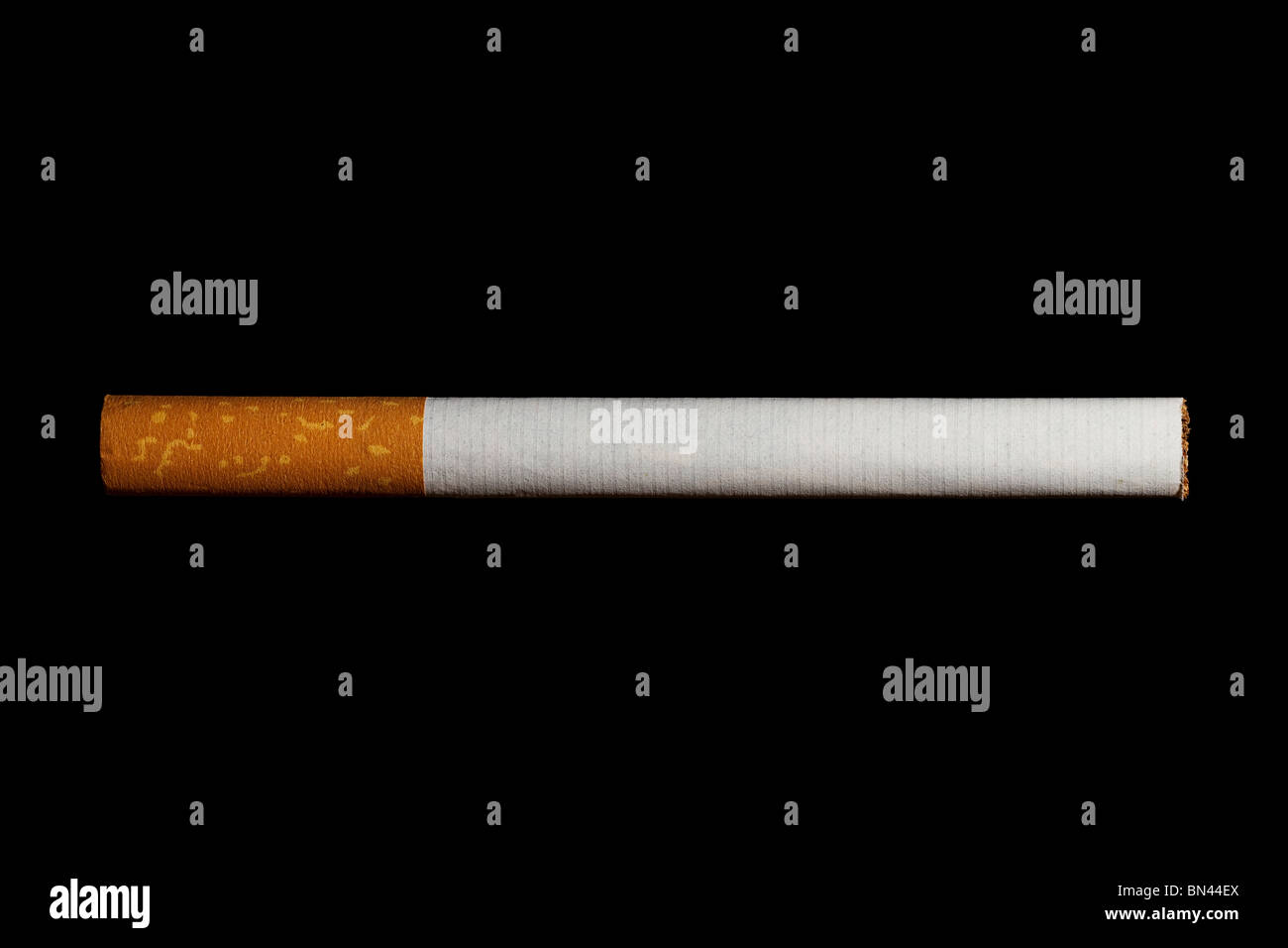 one cigarette with filter isolated on black background - Stock Image