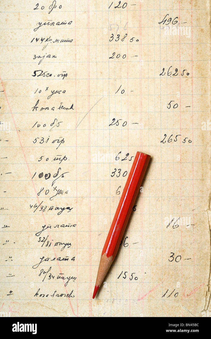 a red pencil on yellowed paper with accounting figures - Stock Image