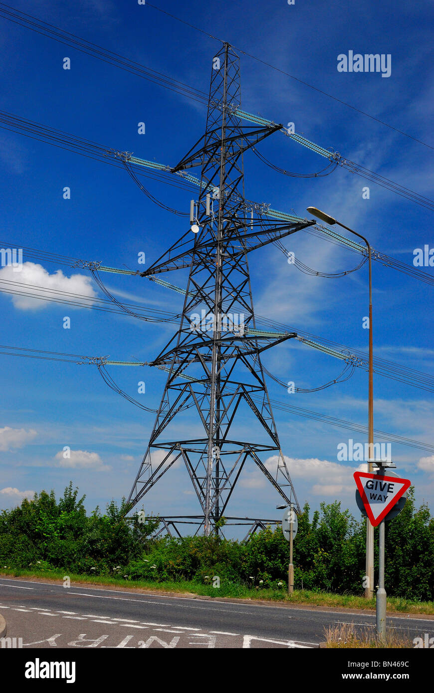 Electricity Pylon next to road junction - Stock Image