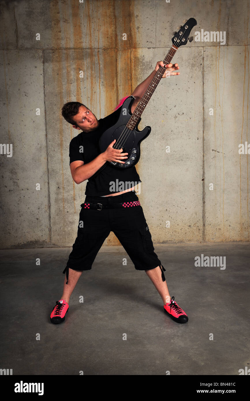 Man playing bass guitar in industrial grunge environment Stock Photo