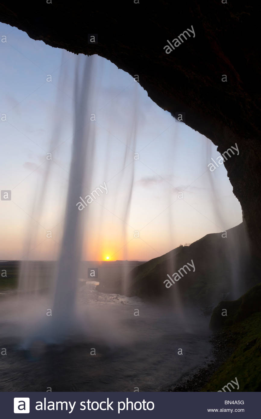 The setting sun shines through the Seljalandsfoss, a 200-foot (60-meter) waterfall in southern Iceland. - Stock Image