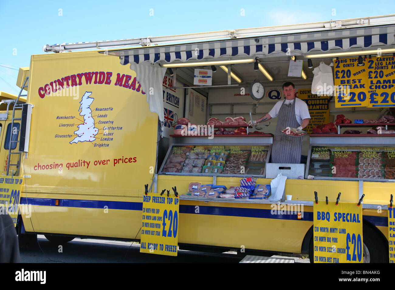 Butcher selling produce from his mobile stall at Dorchester Market - Stock Image