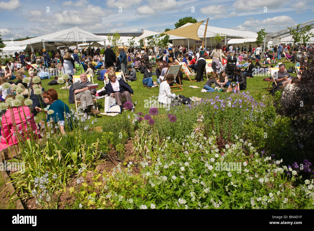 Crowds of people relaxing in the summer sunshine at Hay Festival 2010 Hay on Wye Powys Wales UK - Stock Image