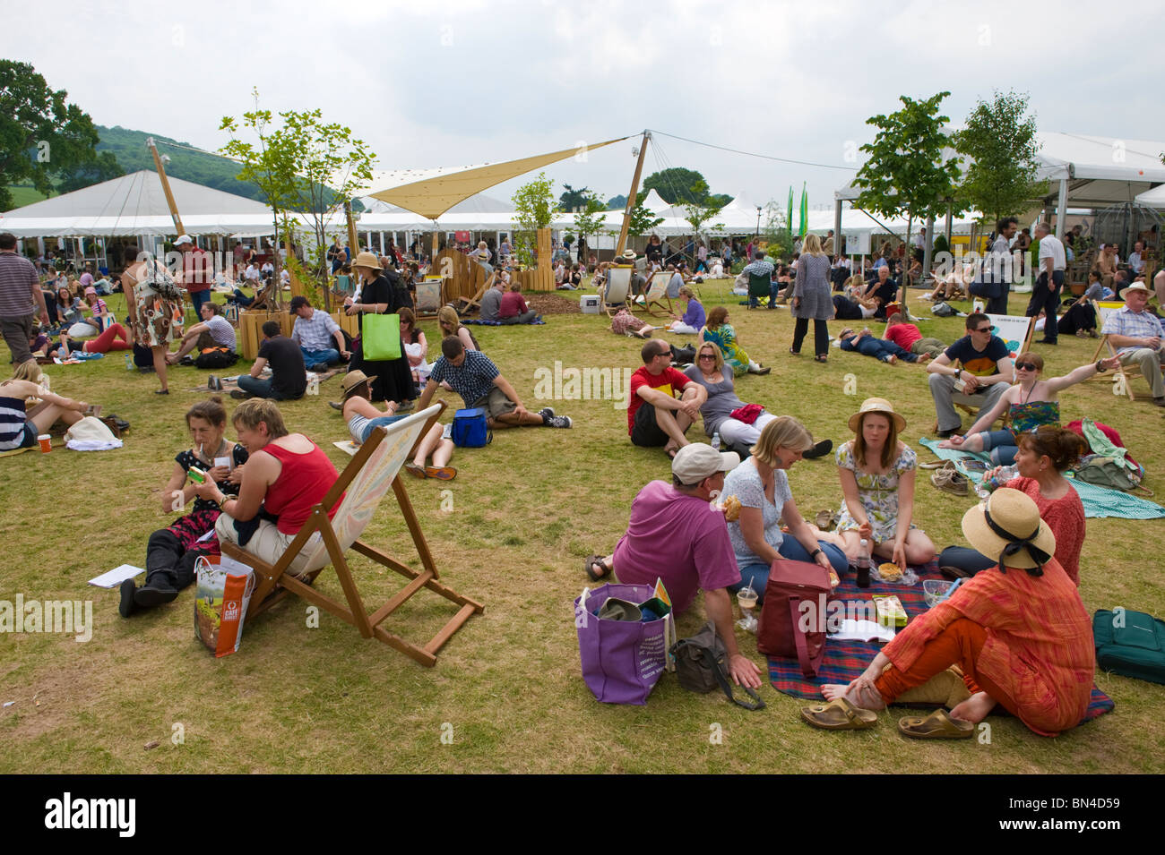 People relaxing on the grass in the summer sunshine at Hay Festival 2010 Hay on Wye Powys Wales UK - Stock Image