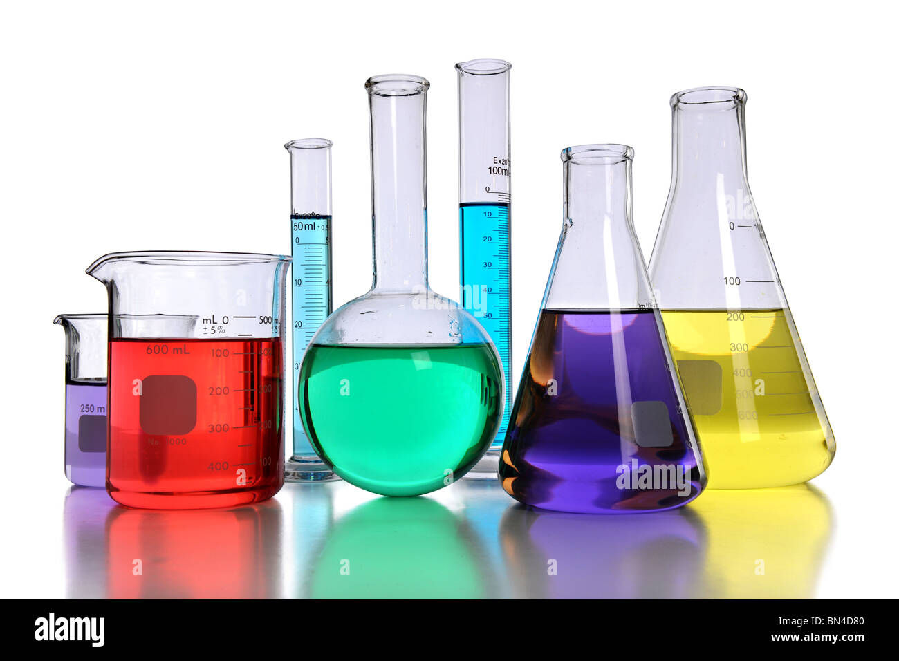 Laboratory glassware with various colored liquids with reflection on table - Stock Image