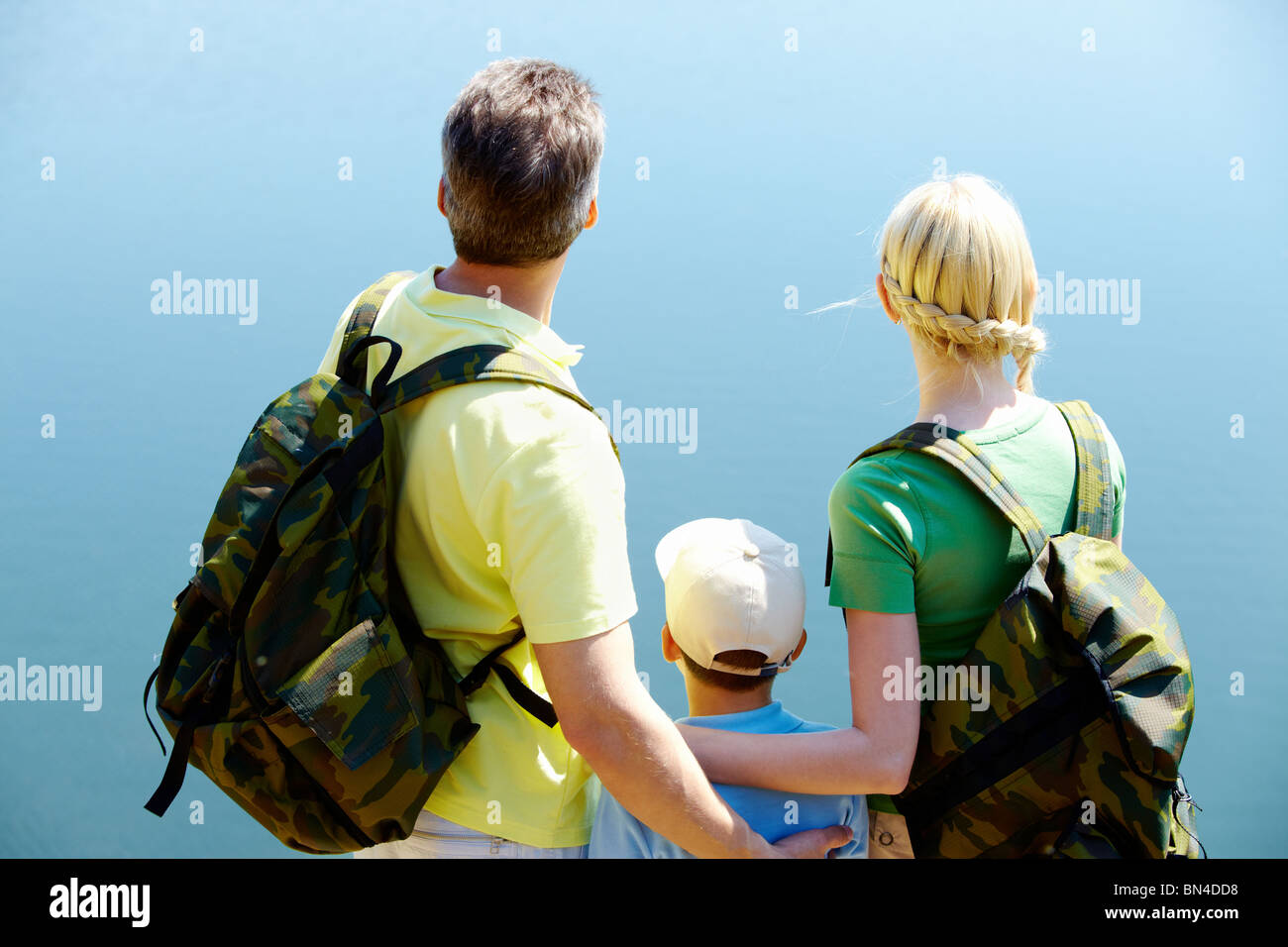 Back view of happy family on blue background Stock Photo