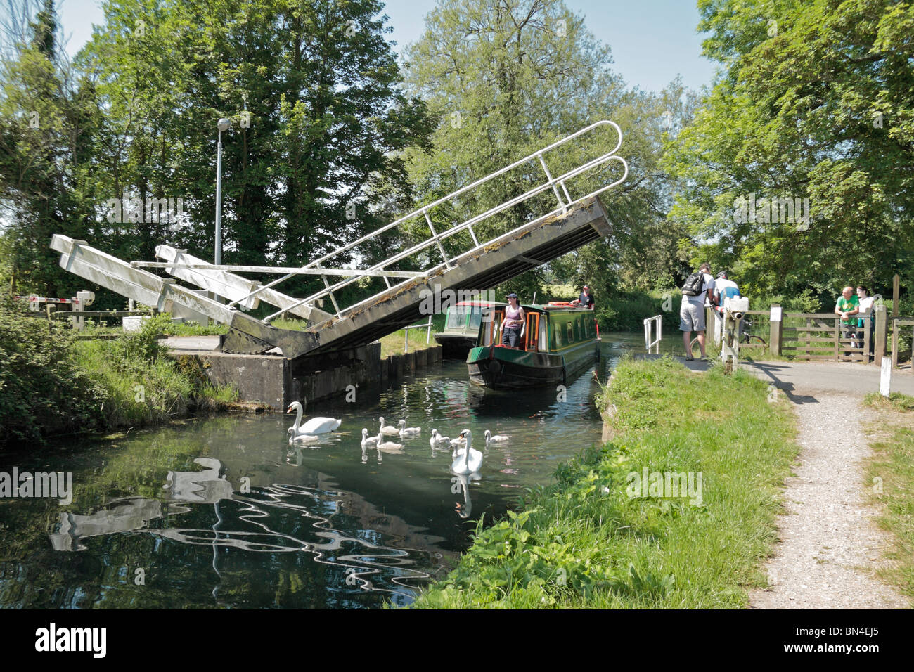 Canal boat passing under the bascule bridge over the Basingstoke Canal near the ruins of Odiham Castle, Hampshire, - Stock Image