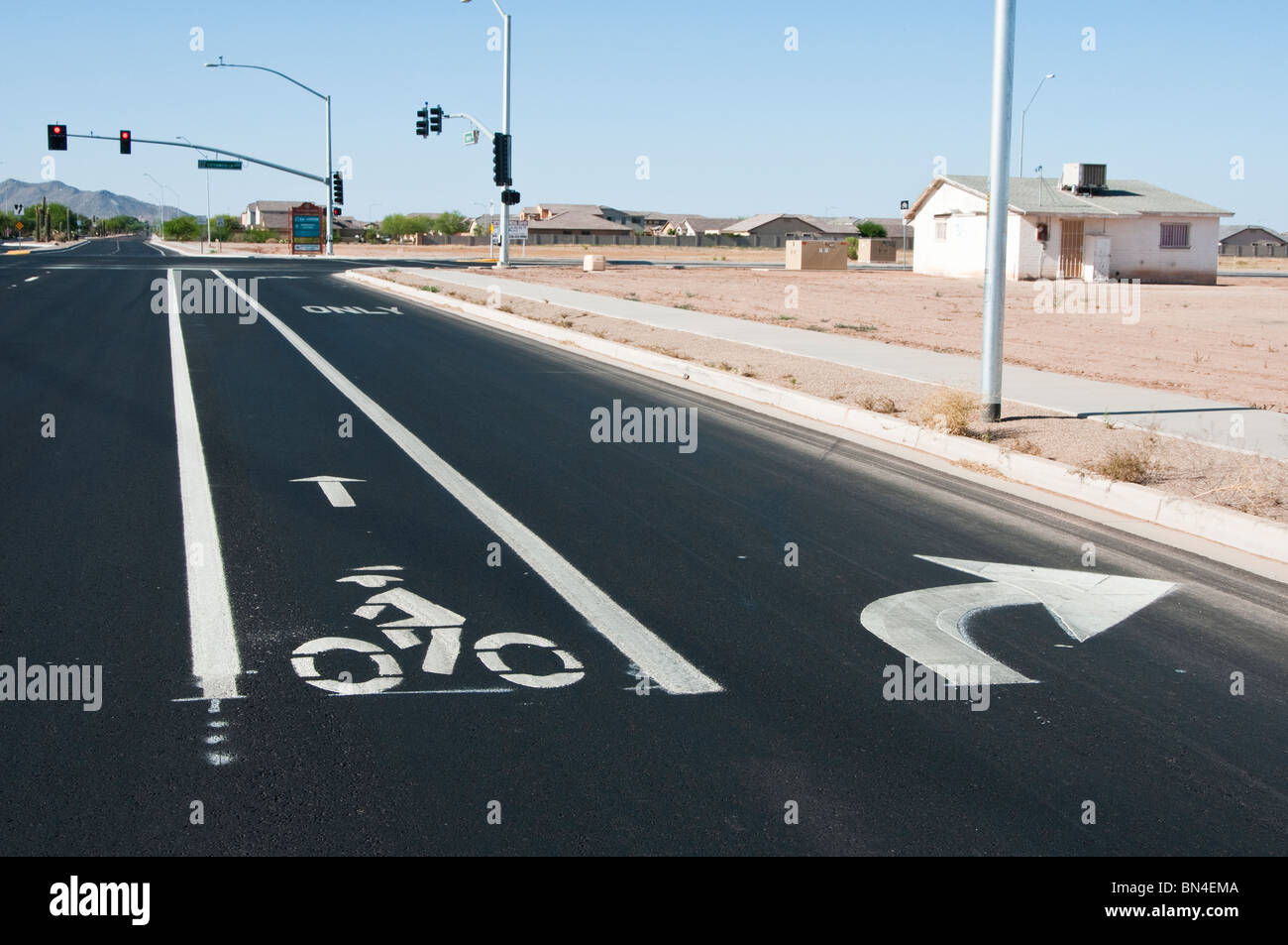 A bike lane is indicated by painted markings on a city street. A right turn lane is on the right. - Stock Image