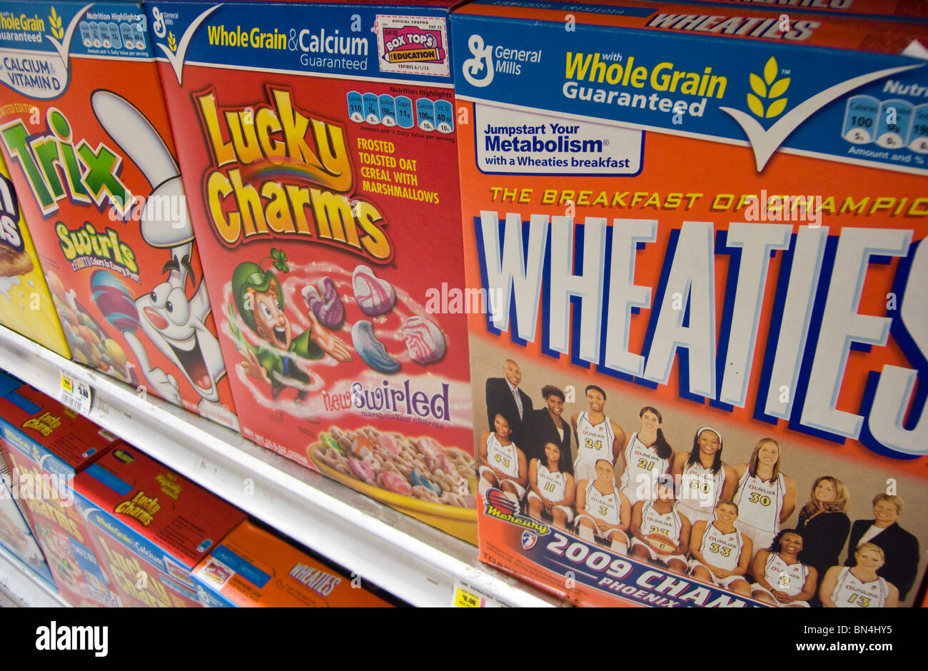 Boxes of General Mills breakfast cereals including Wheaties, Lucky Charms and Trix displayed on supermarket shelves - Stock Image