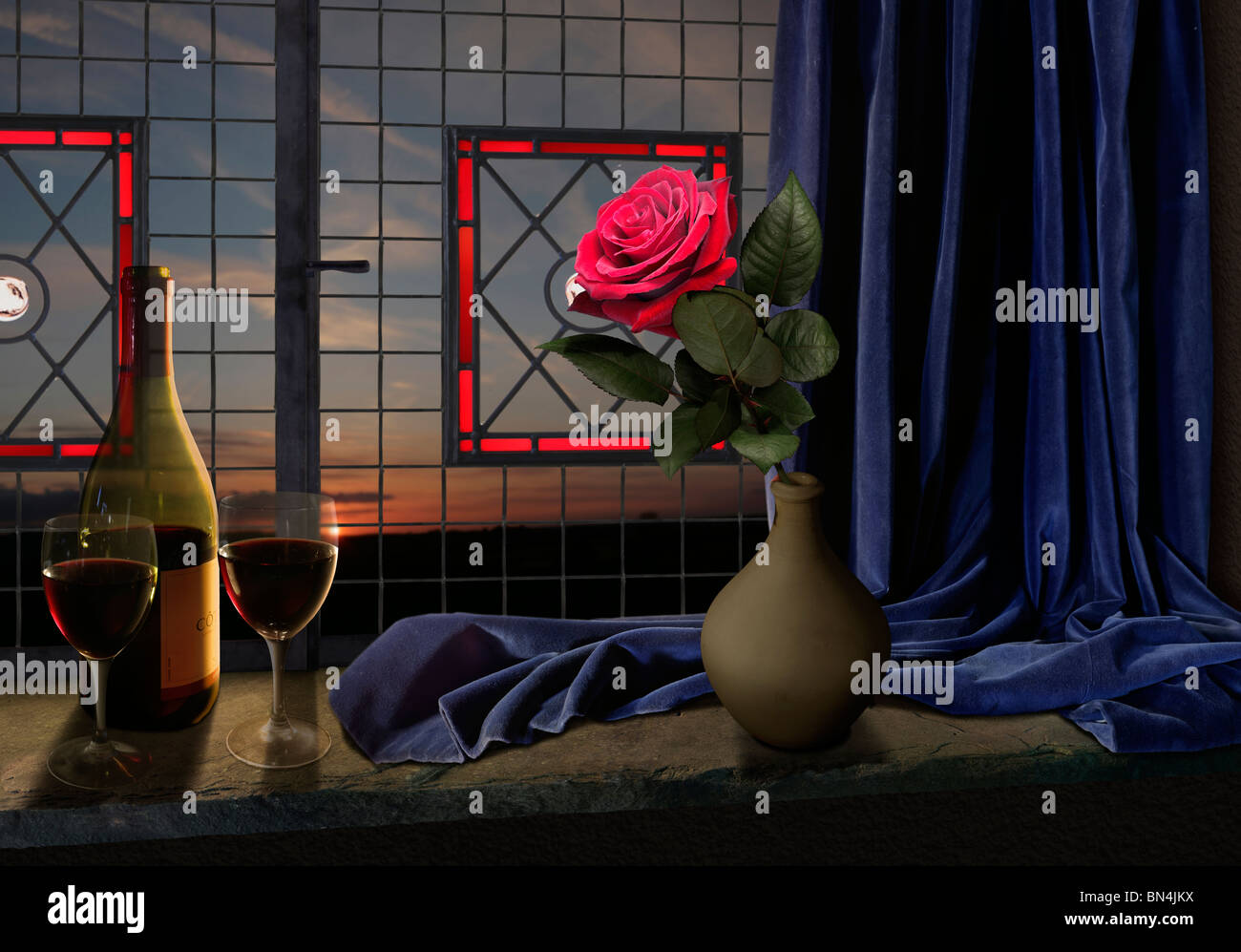 red rose wine and blue curtain on a window seal with sunset - Stock Image