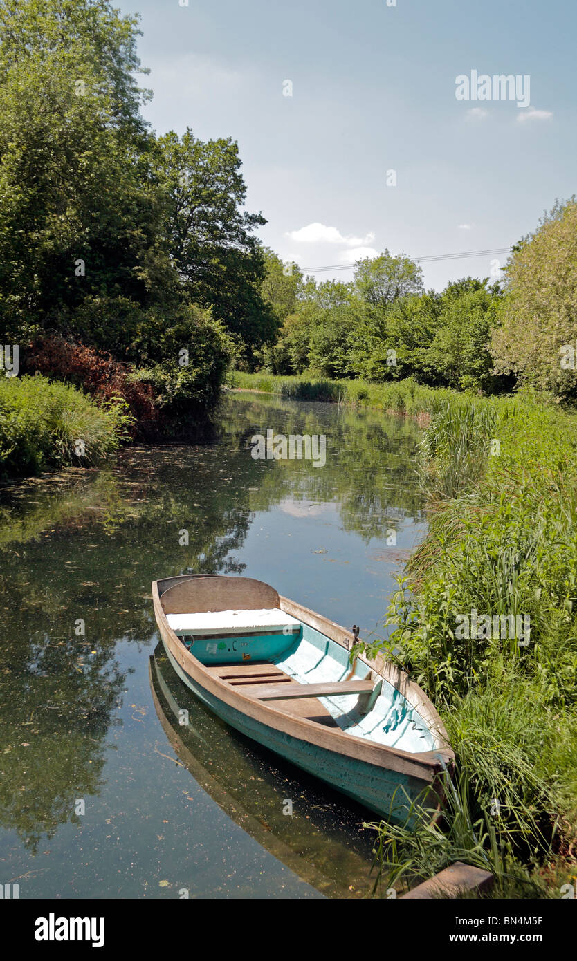 Rowing boat sitting on the Basingstoke Canal near the ruins of Odiham Castle, Hampshire, UK. Jun 2010 - Stock Image