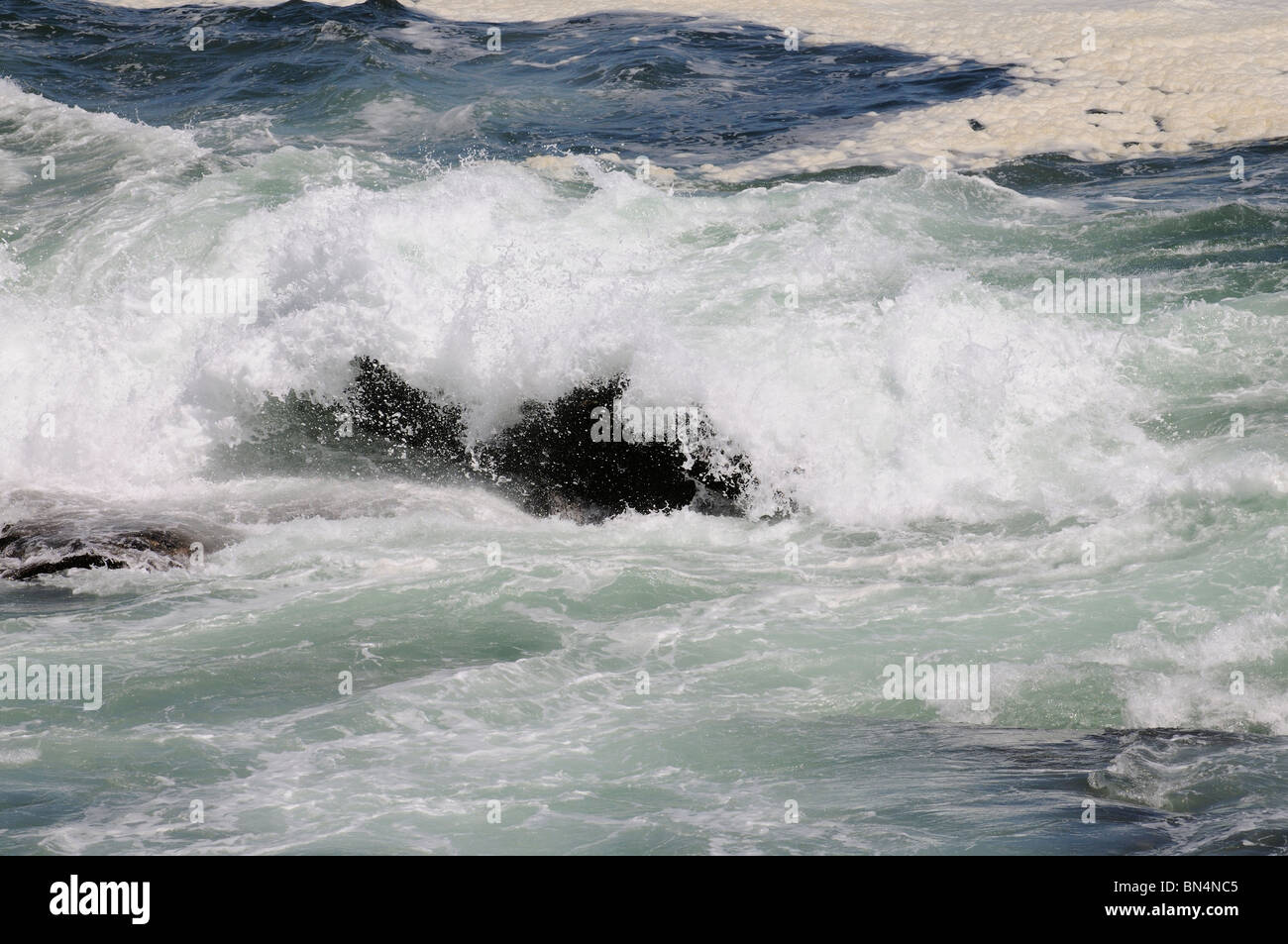 Atlantic Ocean with waves crashing over black rocks Hermanus western Cape South Africa - Stock Image