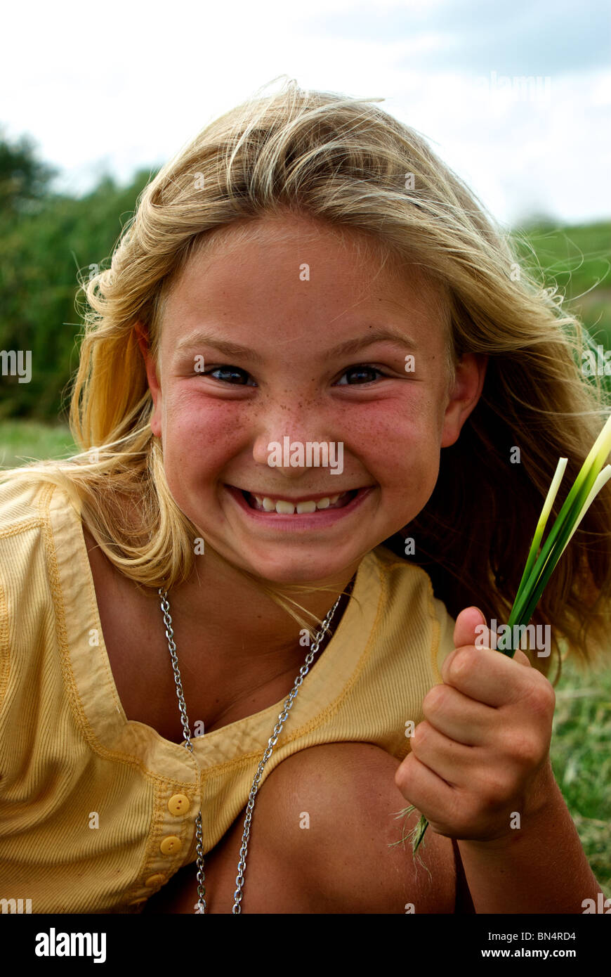 Young pretty smiling blond freckle faced Louisiana girl holding marsh plant stems at Welch's Airboat Tours and Alligator Stock Photo