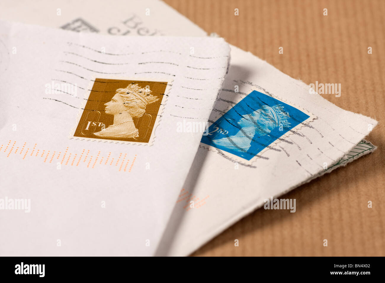 Envelopes with 1st & 2nd class UK postage stamps on brown paper - Stock Image