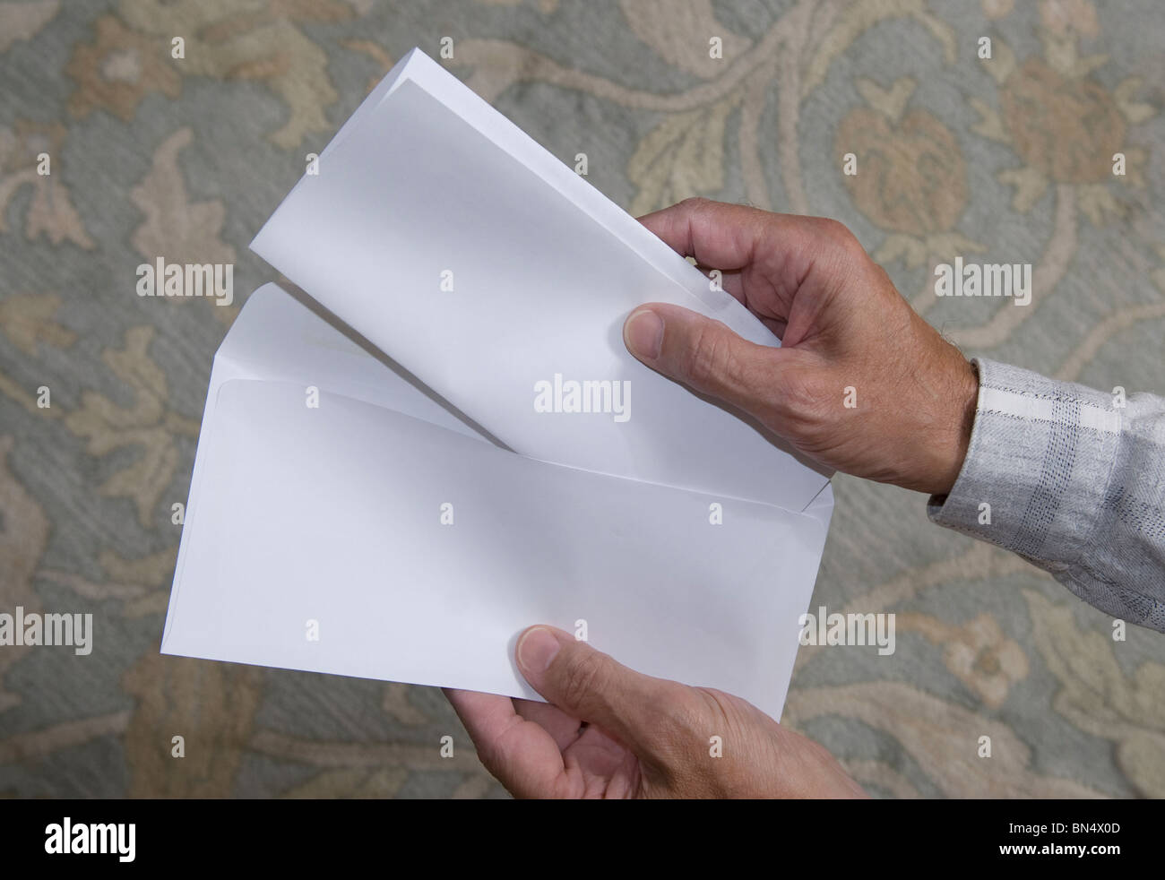 close-up of hands placing document in envelope - Stock Image