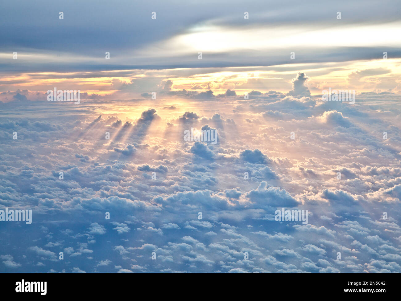 Sun Rays shine through the clouds as dusk approaches - Stock Image