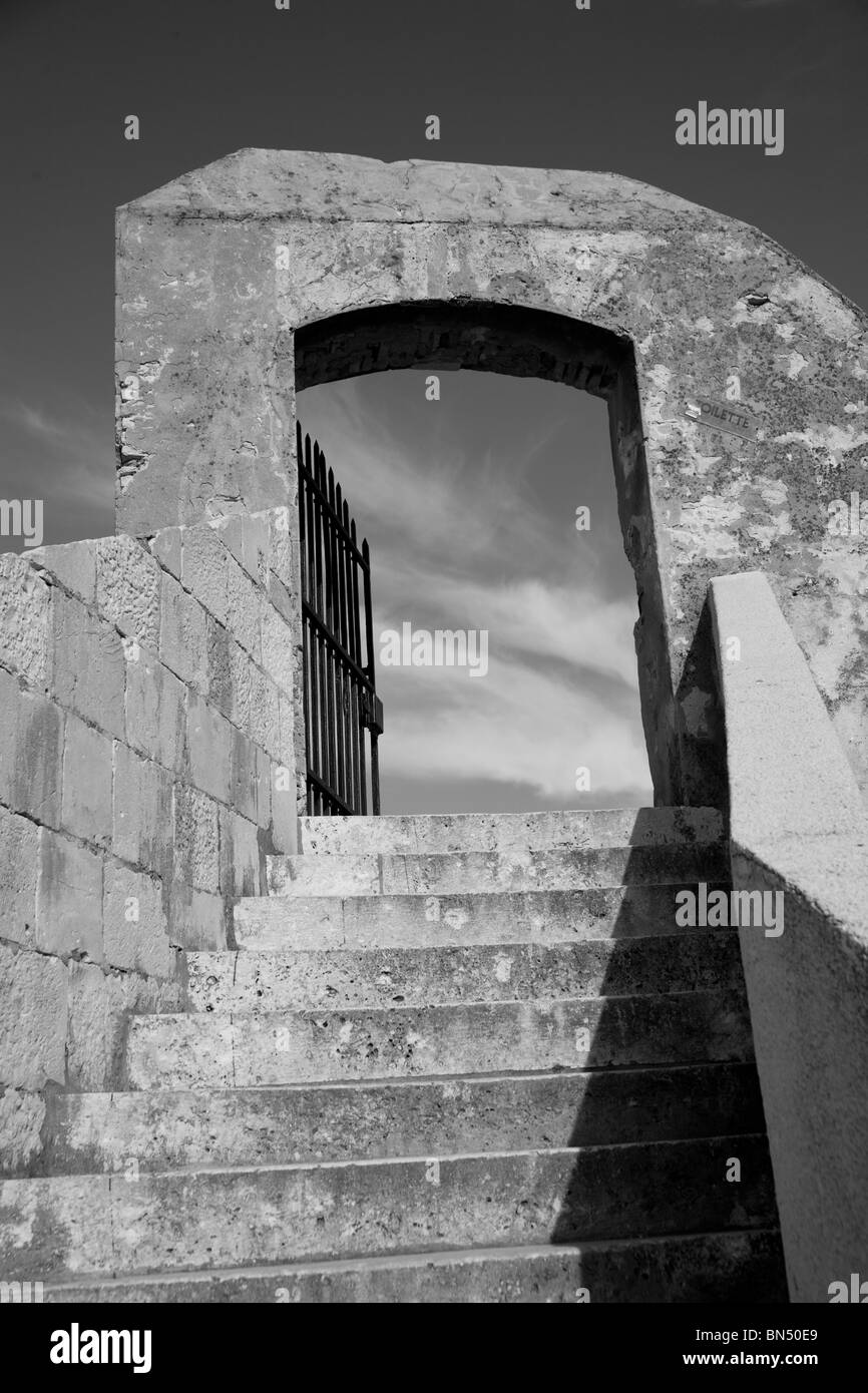 Black and white image of stairs leading up to doorway to the sky and clouds - Stock Image
