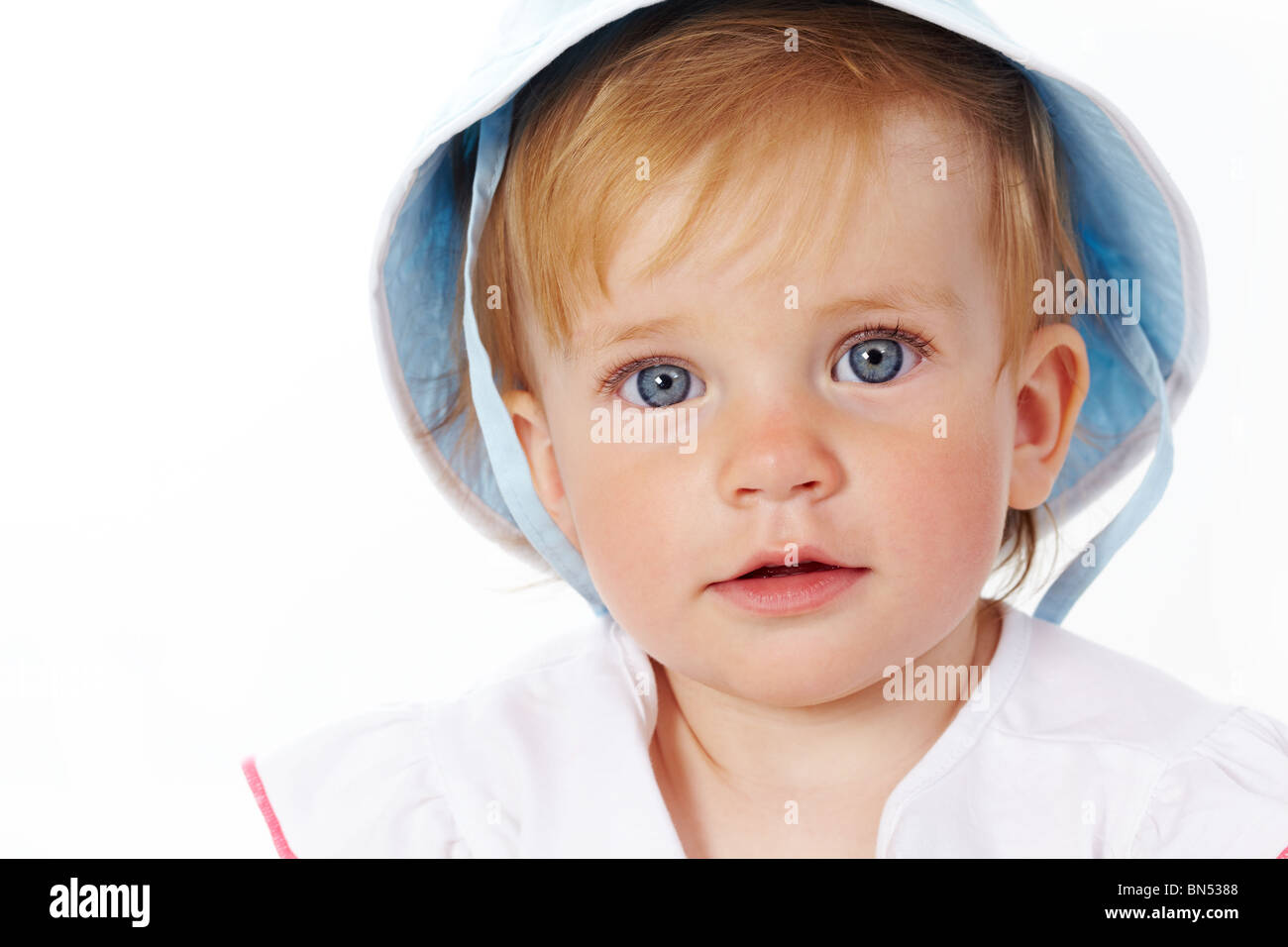 Portrait of cute child looking at camera over white background - Stock Image