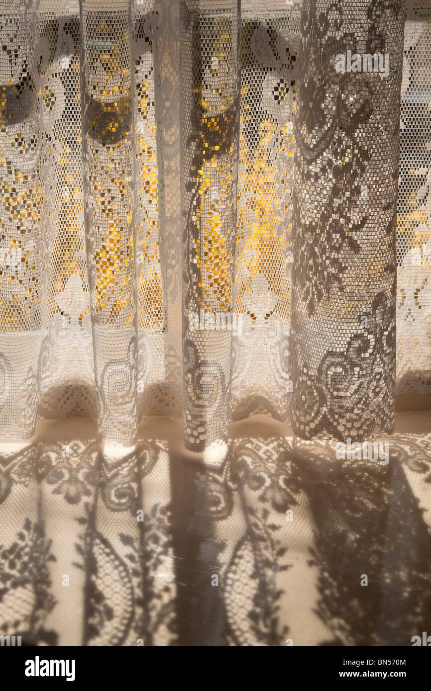 Sunshine through net curtains. - Stock Image