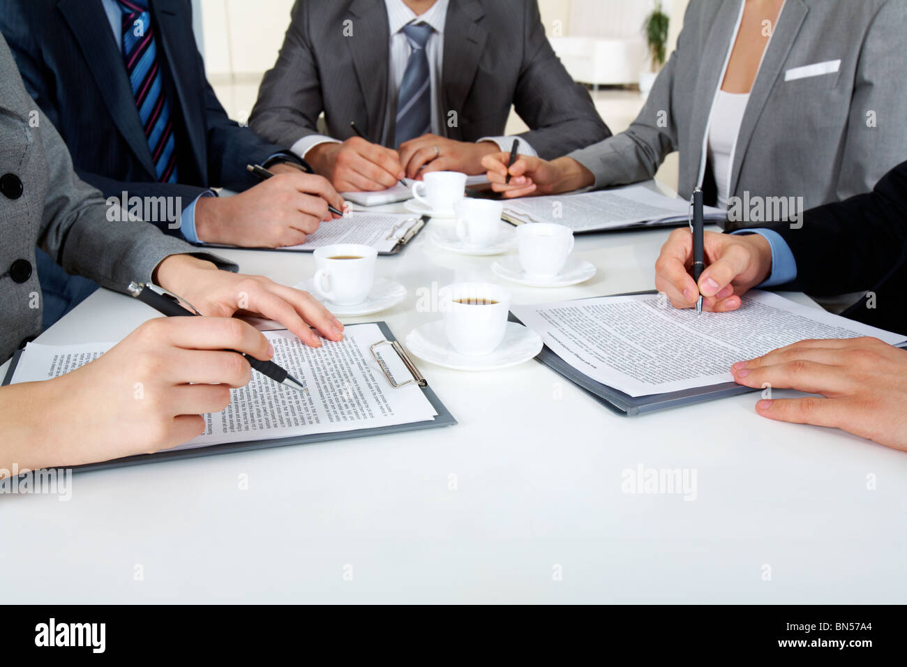 Image of business people hands with ballpoints writing on papers while planning work - Stock Image