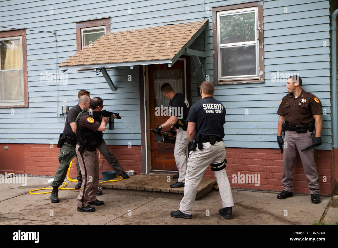 Deputy sheriff's serving drug related search warrant in a rural US community. Narcotics were located inside - Stock Image