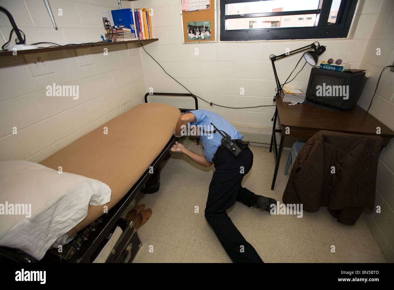 Prison guard, correctional officer, searching the cell of an