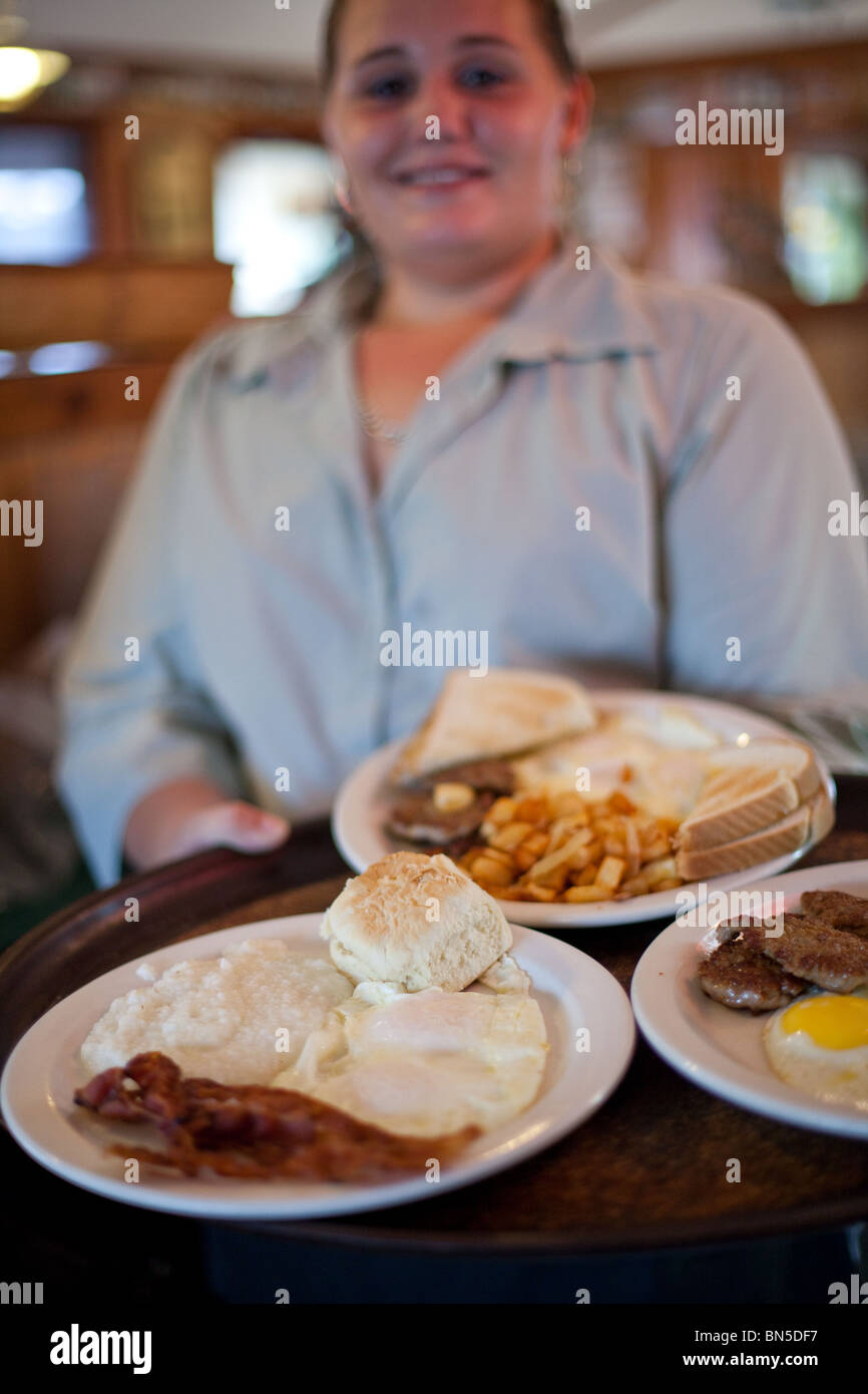 Waitress Sabrina Weeks brings out breakfast orders at Backcountry Cafe, Everglades City, Florida - Stock Image