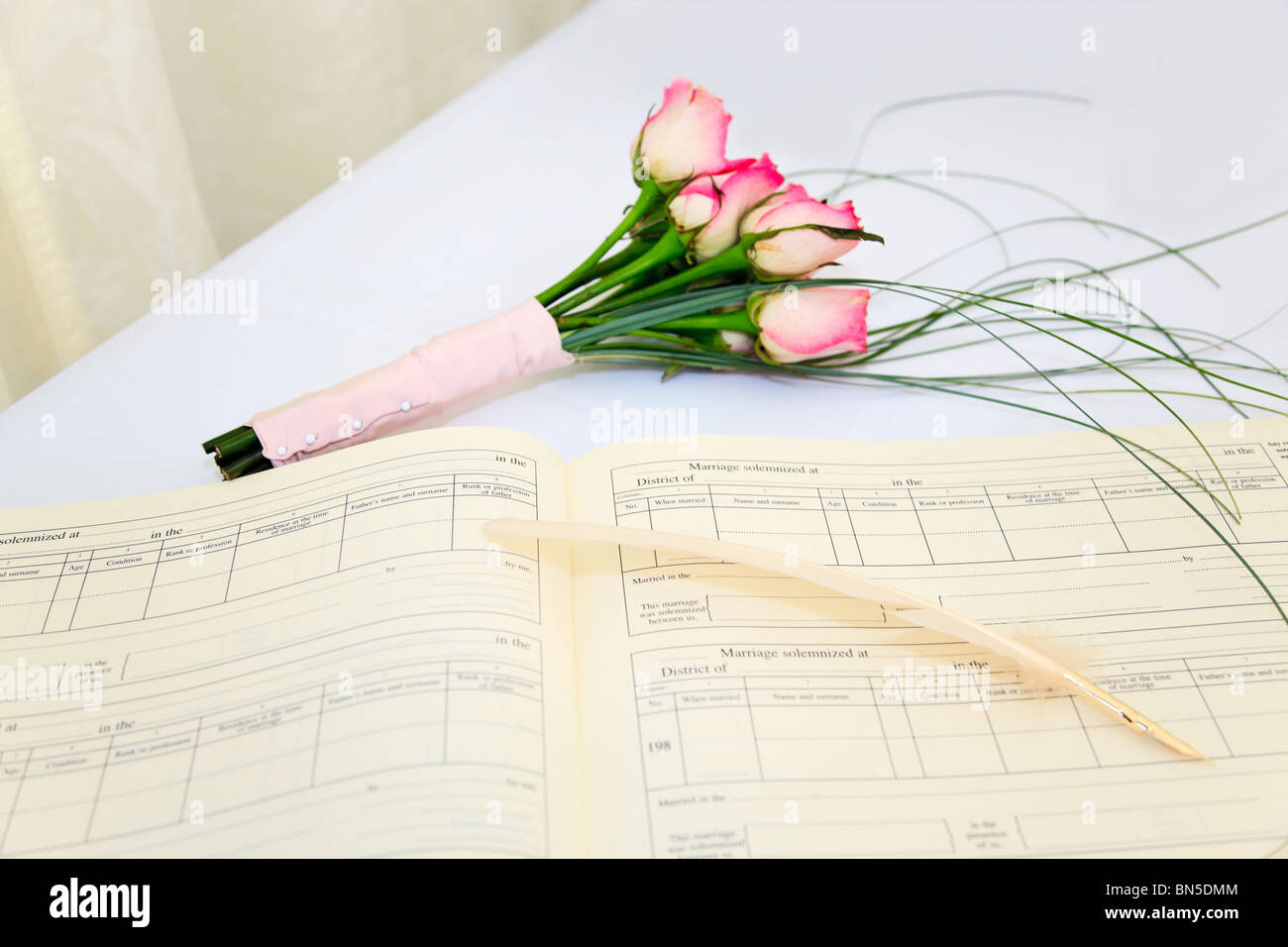 a wedding register and quill with a bouquet of pink roses on a white