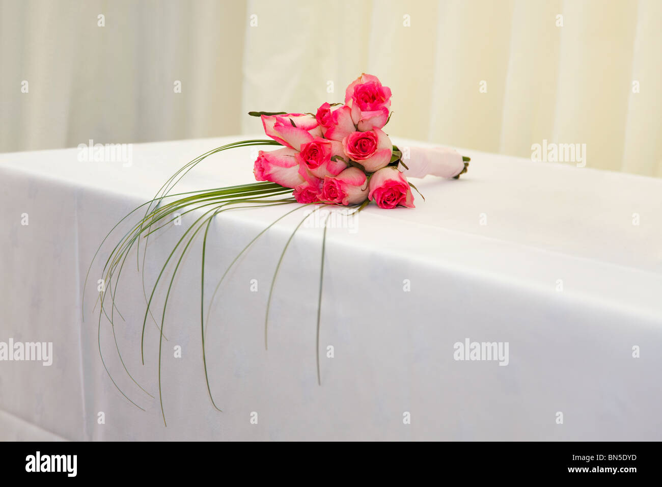 A wedding bouquet of pink roses on a white table with a marquee background. - Stock Image