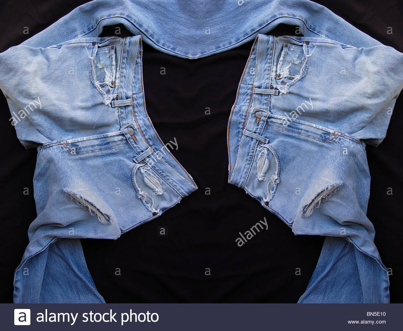 1de0ed2b7bc tabletop birds eye view two pair old used worn torn indigo blue denim jeans  pants on black background showing thread bare fabric