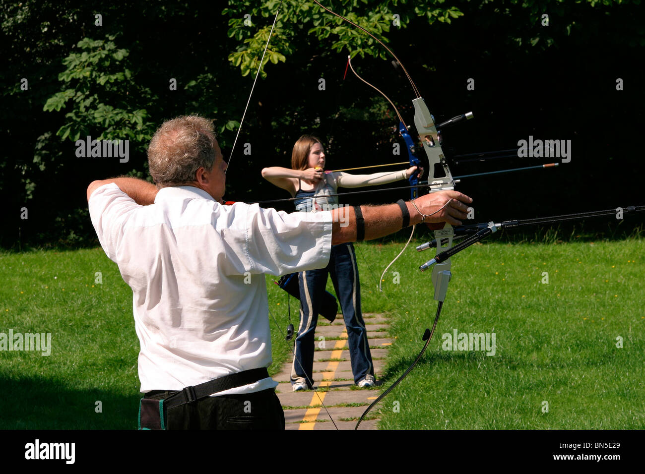 UK, England, Cheshire, Stockport, Cheadle, Bruntwood Park, male and female archers drawing bows in archery group - Stock Image