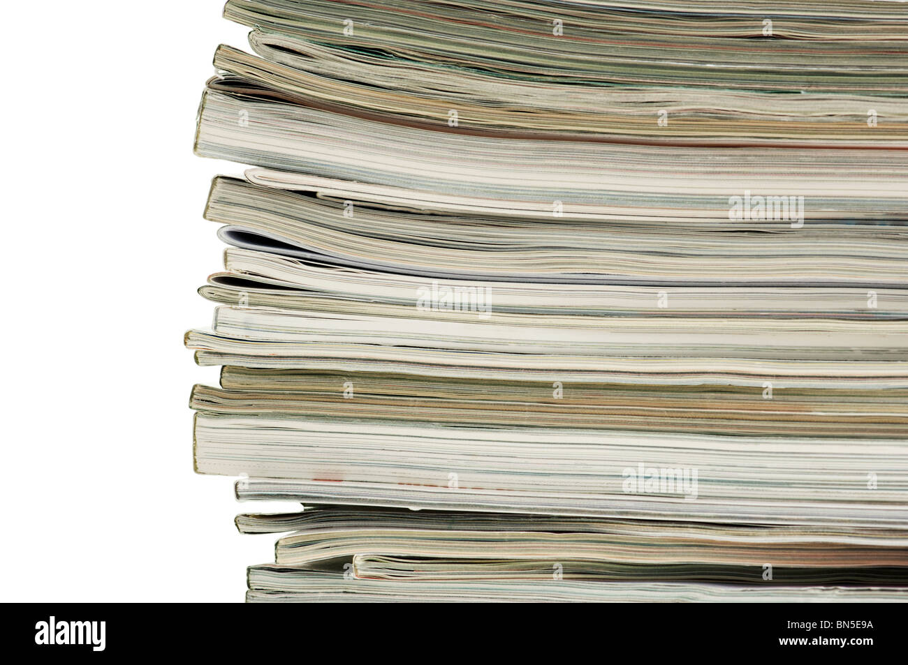 Horizontal image of the spine and ends of a stacked pile of magazines. - Stock Image