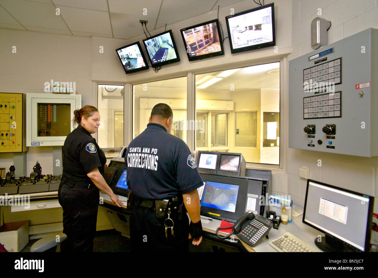 Uniformed  Hispanic corrections officers operate the electronic security center of the Santa Ana, CA, city jail. - Stock Image
