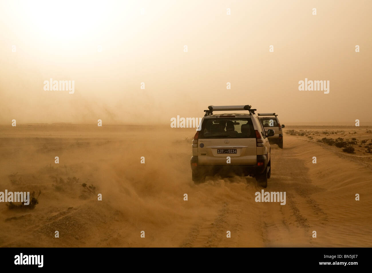 Four wheel drive vehicles drive on a track through the Sahara Desert in Tunisia. - Stock Image