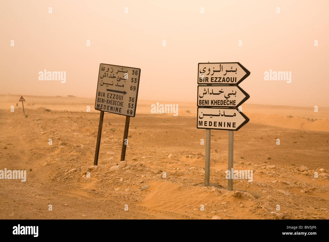 Road signs in the Sahara Desert are written with Arabic and Latin letters. - Stock Image
