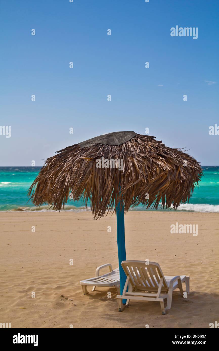Straw umbrella on beach - Stock Image