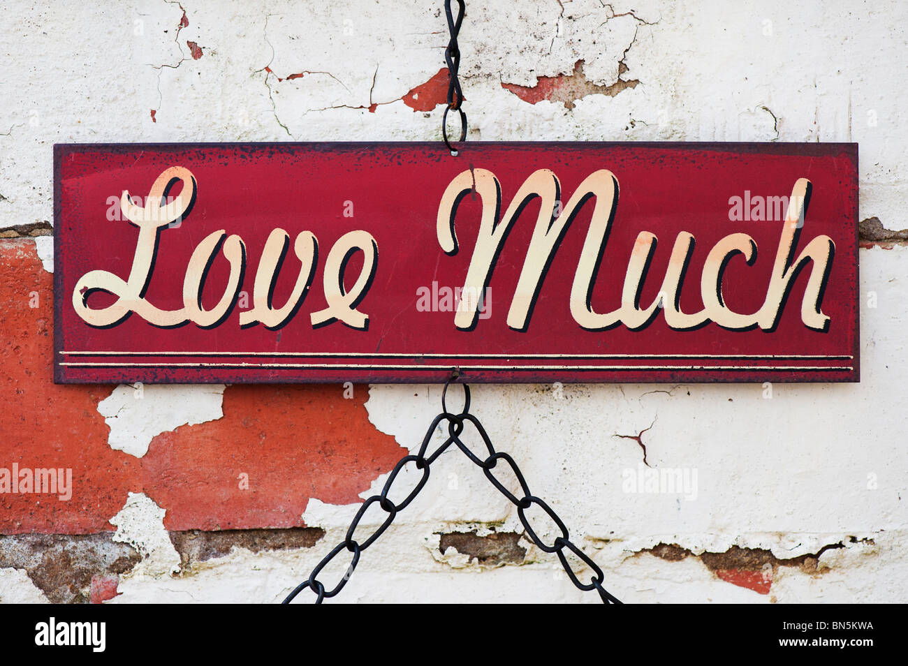 Love much. Old metal garden sign on a painted brick wall - Stock Image