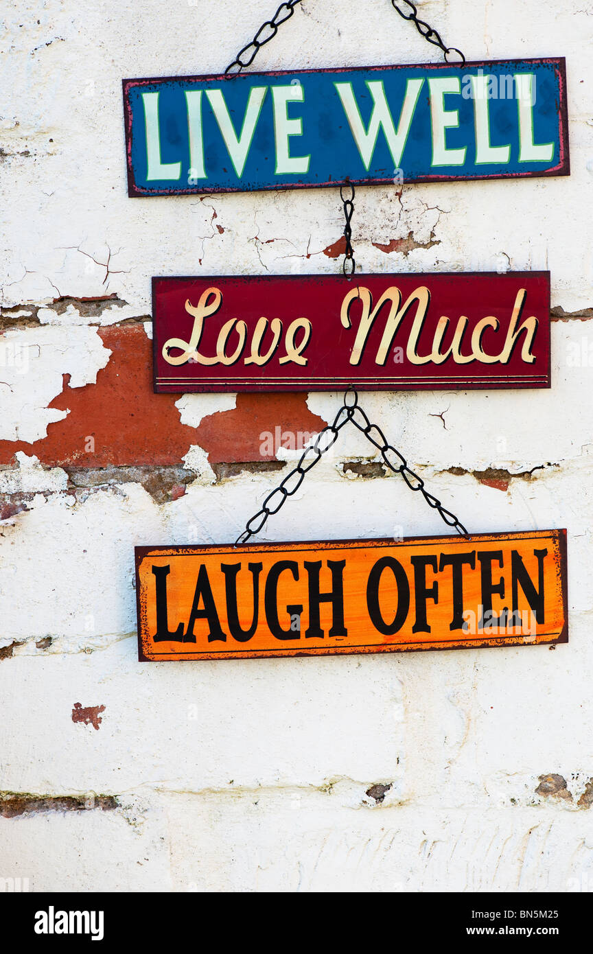 Live, Love, Laugh, old metal garden signs on a painted brick wall - Stock Image