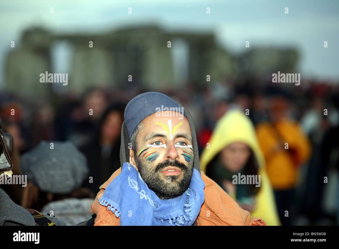 Reveller watching the sunrise summer solstice at Stonehenge - Stock Image