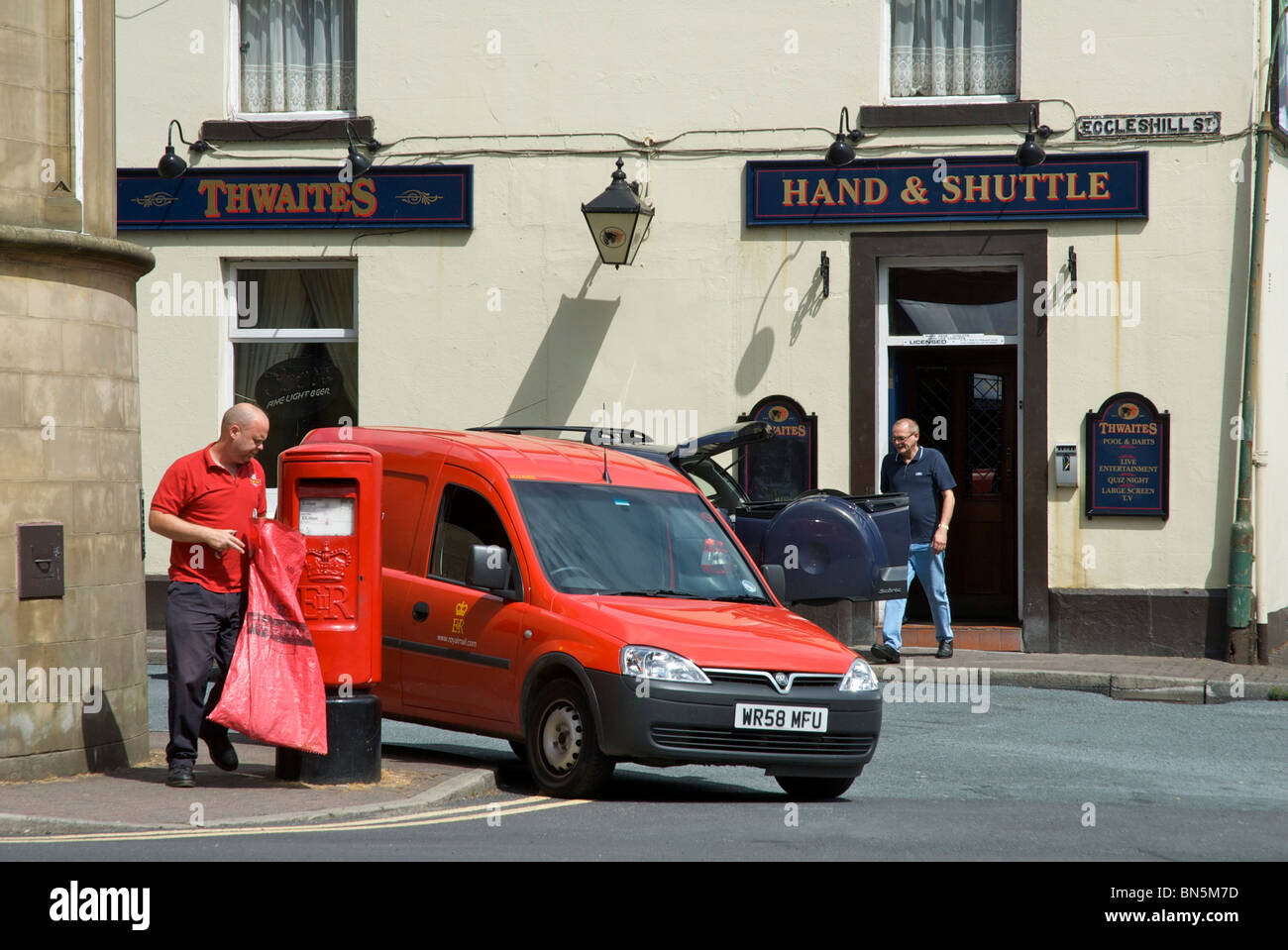 Postman emptying post-box in front of Hand & Shuttle pub, Padiham, Lancashire, England UK - Stock Image
