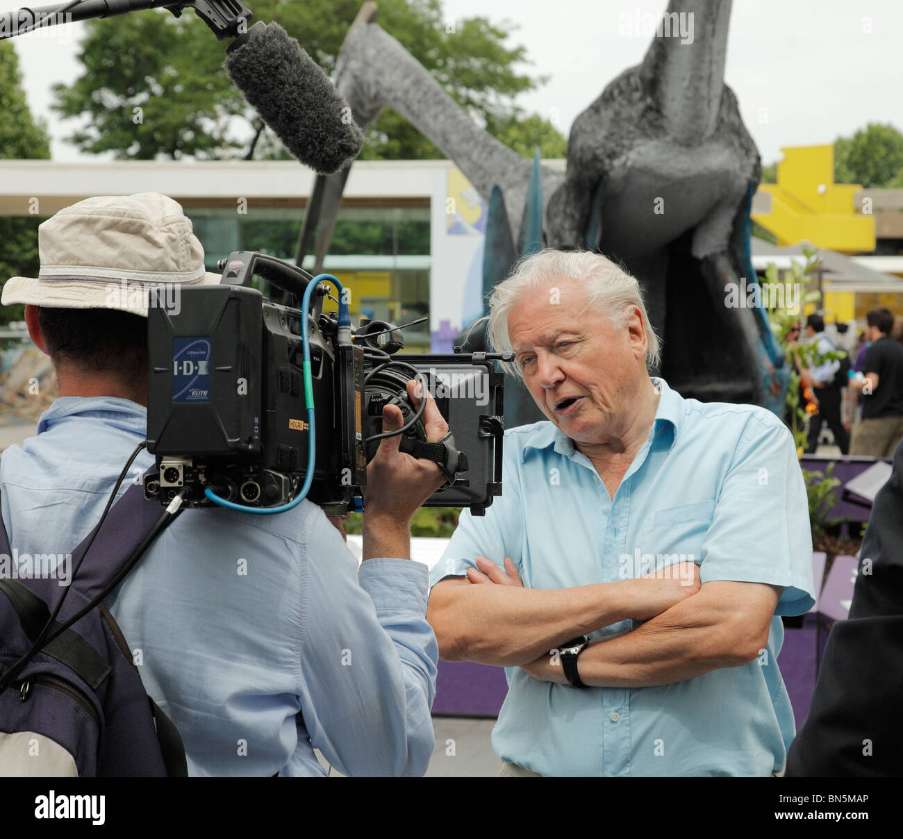 Sir David Attenborough being filmed beside an exhibition of Pterosaurs at the Southbank Centre, London. - Stock Image