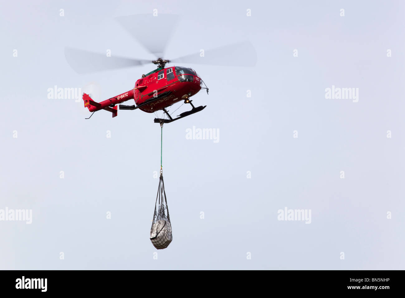 Helicopter carrying a load; Cornwall - Stock Image