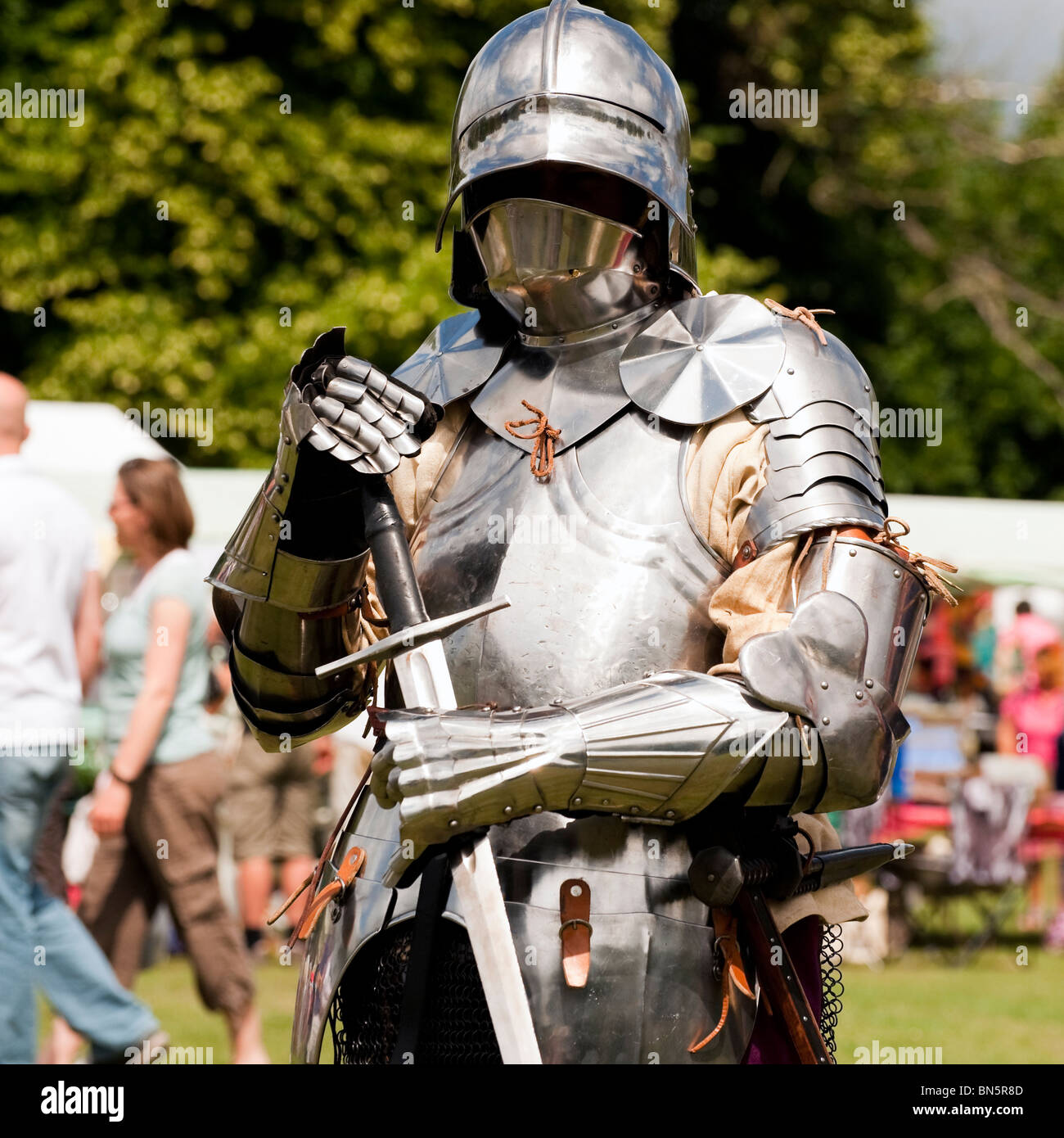 Man wearing suit of armor at the Castle Green, Hereford, UK. Medieval reenactment knight with a broadsword. - Stock Image