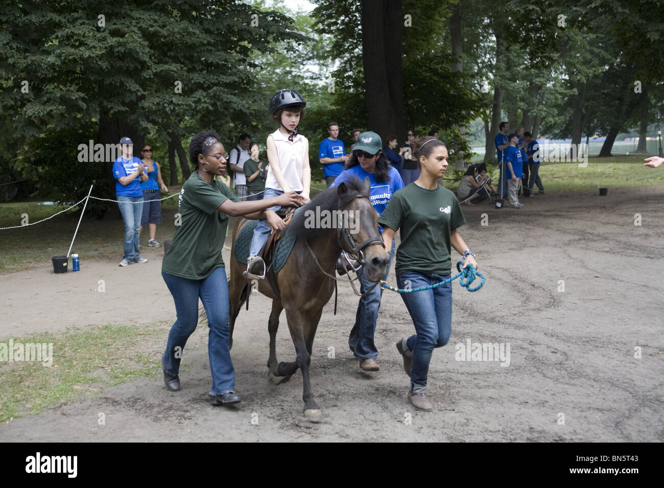 Disabled children receive developmental therapy learning to ride horses, known as Hippotherapy. - Stock Image