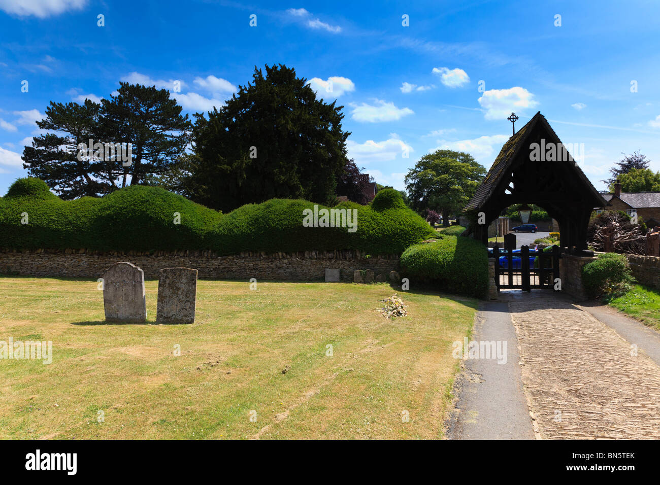 The Lychgate and yew hedge around the Churchyard of All Saints Church, Turvey, Bedfordshire, UK - Stock Image